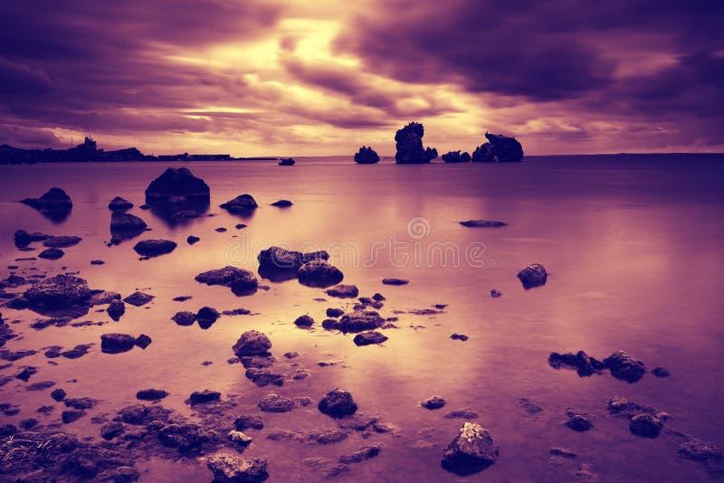 Sunrise over a rocky seashore. Dramatic cloudy sky before sunrise over a rocky seashore royalty free stock image