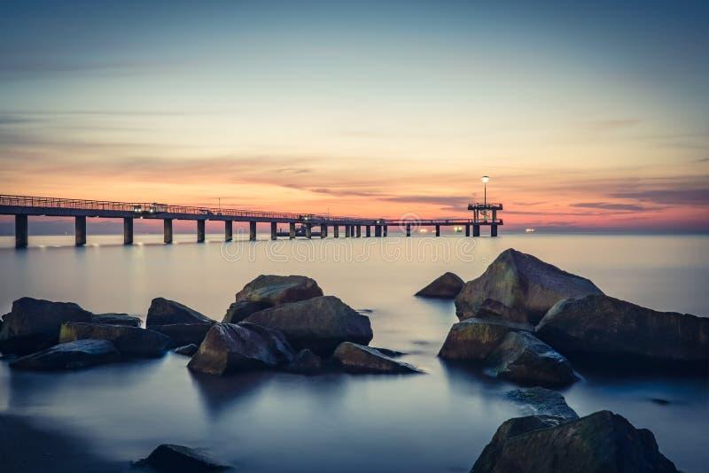 Sunrise over the sea bridge in Burgas bay. Vintage effect. royalty free stock image