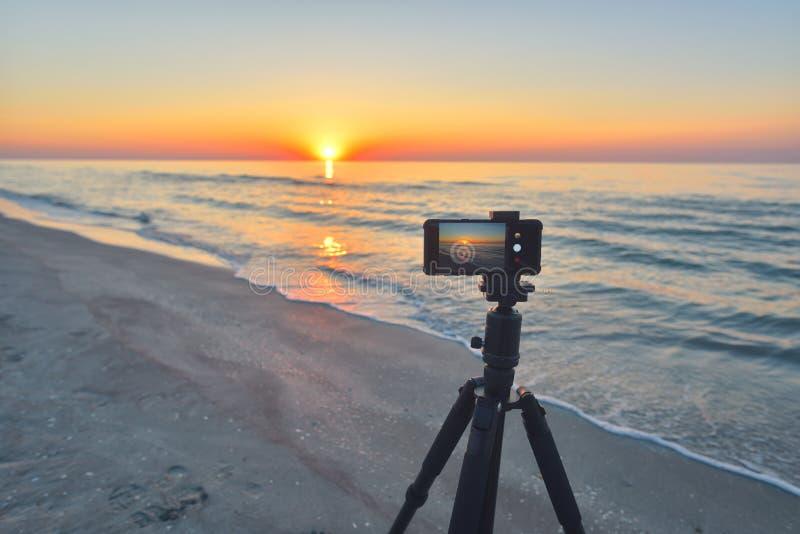 Sunrise over the sea coast. Fireball of the sun above the horizon in a colorful orange sky. Smartphone camera on a tripod in royalty free stock photo