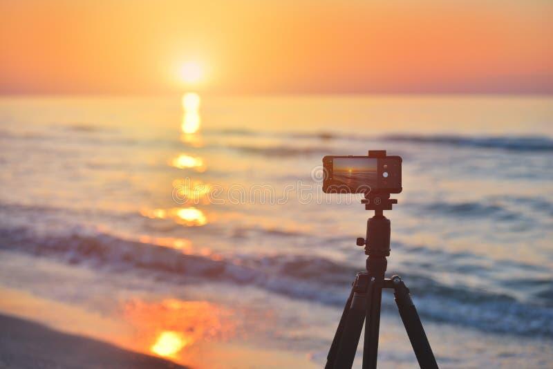 Sunrise over the sea coast. Fireball of the sun above the horizon in a colorful orange sky. Smartphone camera on a tripod in stock photo