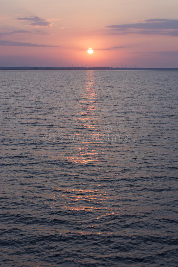 Sunrise over the sea horizon. Sun rising over the blue sea horizon showing off it's beautiful colors in he skies and water. Shot from a ferry. Colors are not royalty free stock photos