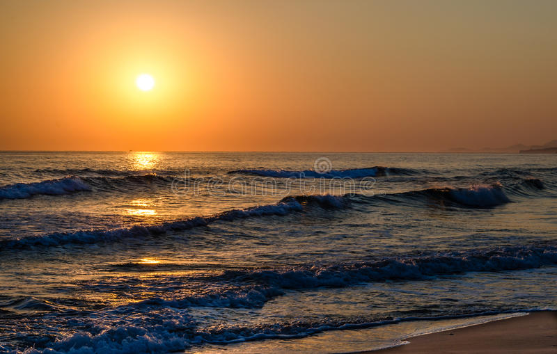 Sunrise over the sea, the rolling calm waves, sandy beach. Skay orange, waves blue royalty free stock images