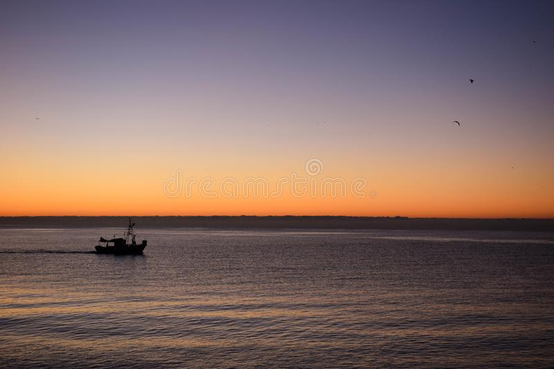 Sunrise over the sea. Shilouette of a ship before start fishing with a beautiful sunrise on the background royalty free stock image