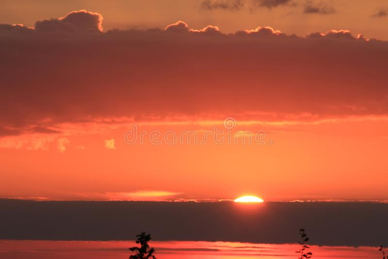 Sunrise over the sea. Sky, clouds and the sea in the rays of the rising sun stock images