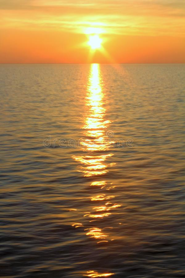 Sunrise over the sea with the sun rising over the horizon stock photo