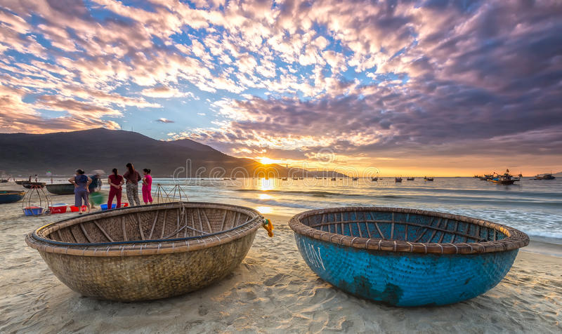Sunrise over seaside. Da Nang, Vietnam, June 26, 2015: Sunrise over seaside with sunlight to create stars and double pannier foreground boat, people exercising royalty free stock photos