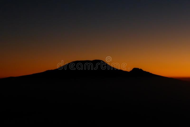 Sunrise over the silhouette of Mount Kilimanjaro and Mawenzi in Tanzania royalty free stock photo