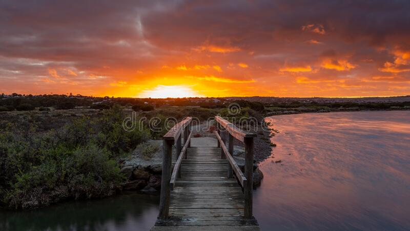 Sunrise over the small foot bridge located on the Onkaparinga River in Port Noarlunga South Australia on 30th March 2020 stock image