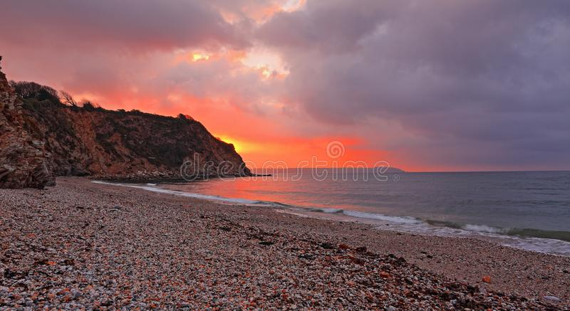 Sunrise over the stony beach at Charlestown, Cornwall. The sunrise lights up the sea and heavily cloudy skies at Charlestown in Cornwall royalty free stock image