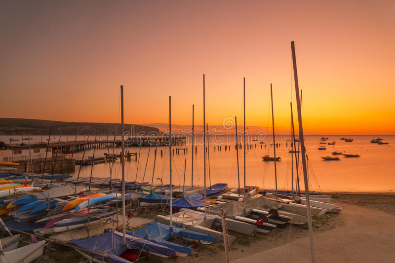 Sunrise over Swanage piers illuminated by the orange pre-dawn. Boats, the new and old piers are illuminated by the orange pre-dawn royalty free stock photos