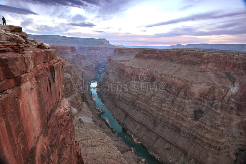 Sunrise over Toroweap canyon,North Rim,Grand Canyon, Arizona. A spectator watches sunrise over breathtaking panoramic eroded rock layers steep descent valley stock photo
