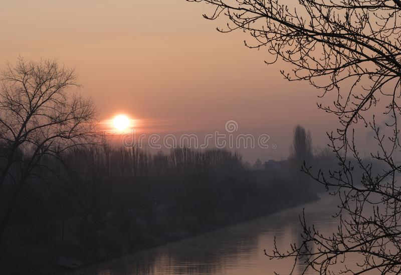 Sunrise over a waterway in Berlin at a misty morning. Sunrise over the waterway Teltowkanal in Berlin, Germany at a misty morning with reflections on the surface royalty free stock photo