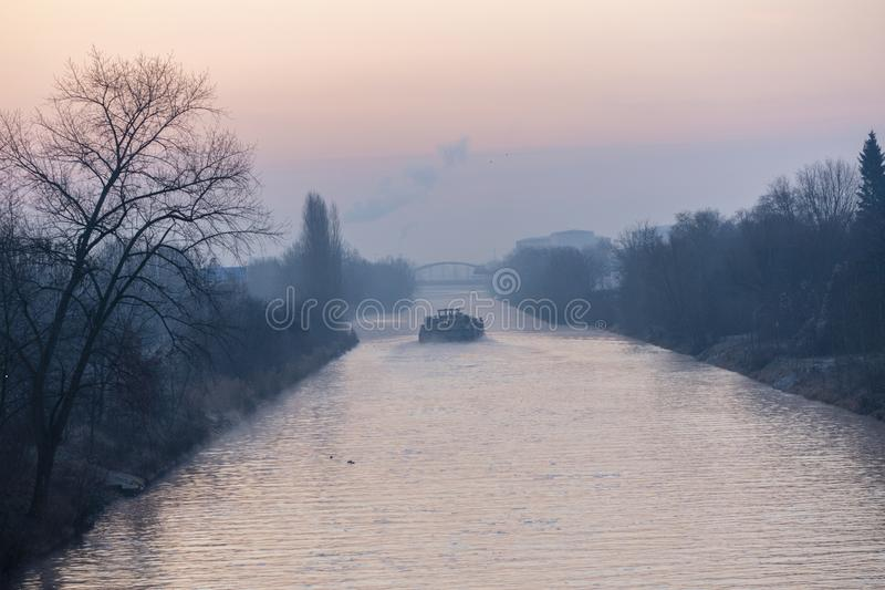 Sunrise over a waterway in Berlin at a misty morning with view to a freighter and a bridge in background. Sunrise over the waterway `Teltowkanal` in Berlin stock images