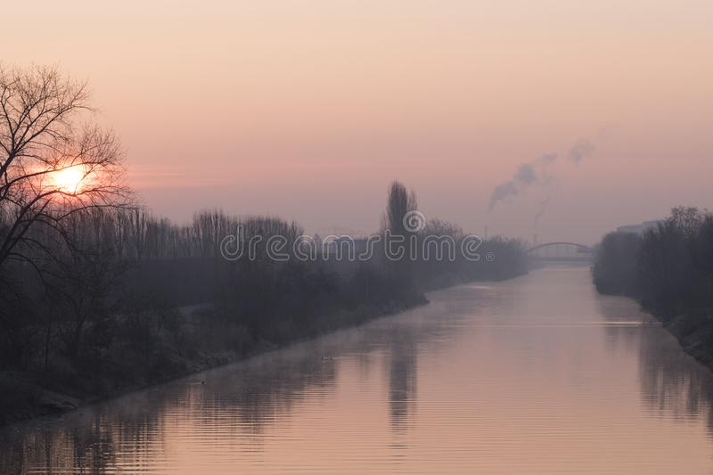 Sunrise over a waterway in Berlin at a misty morning with view to a bridge in background. Sunrise over the waterway `Teltowkanal` in Berlin, Germany at a misty royalty free stock photography