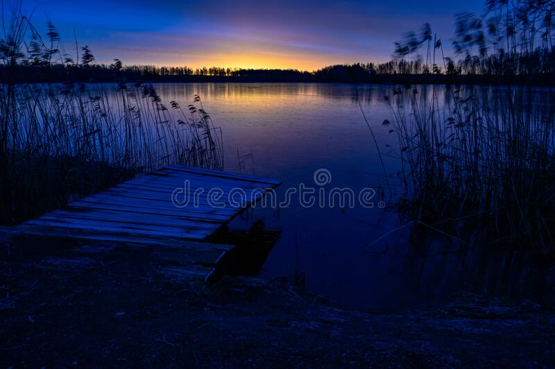 Sunrise over wooden jetty and frozen lake stock photography