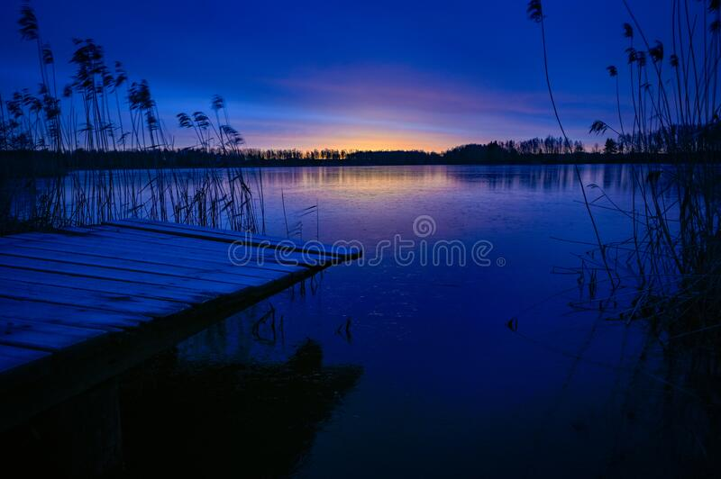 Sunrise over wooden jetty and frozen lake royalty free stock photo