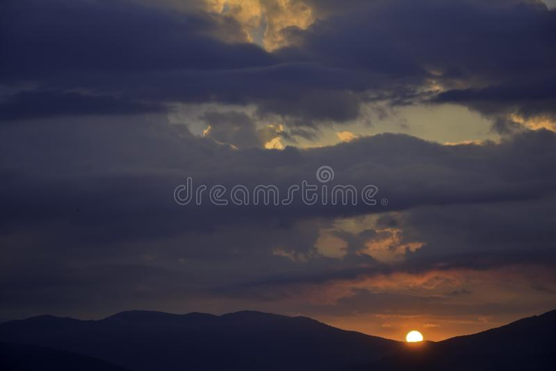 Sunrise in overcast sky. Over the mountains stock images