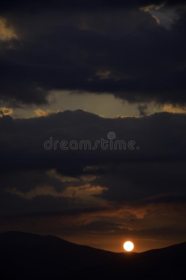 Sunrise in overcast sky. Over the mountains royalty free stock photo