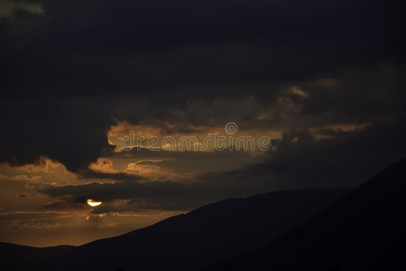 Sunrise in overcast sky. Over the mountains royalty free stock photos