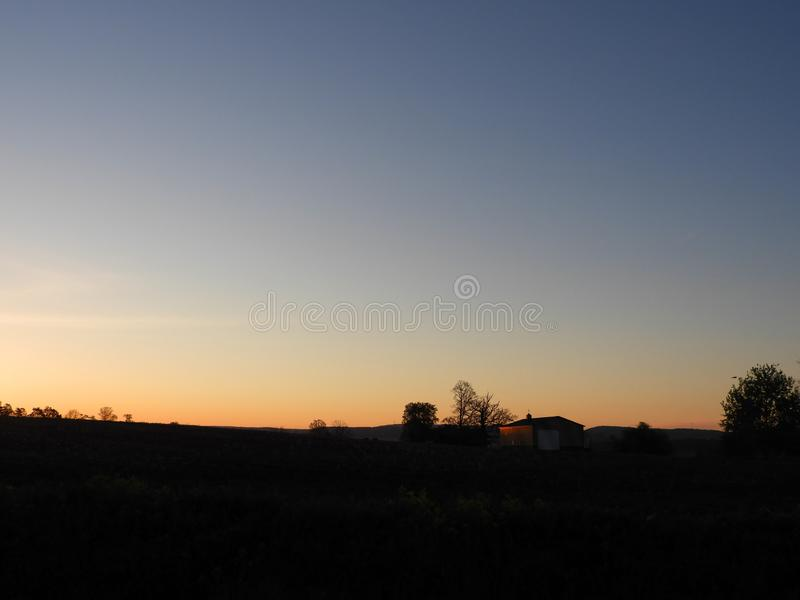 Sunrise peaks from behind a hill with pole barn silhouette royalty free stock photo