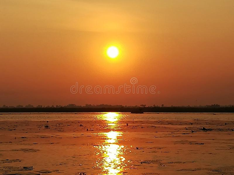 The sunrise is reflected in the water in dark orange color. Sunrise reflected water dark orange color stock image