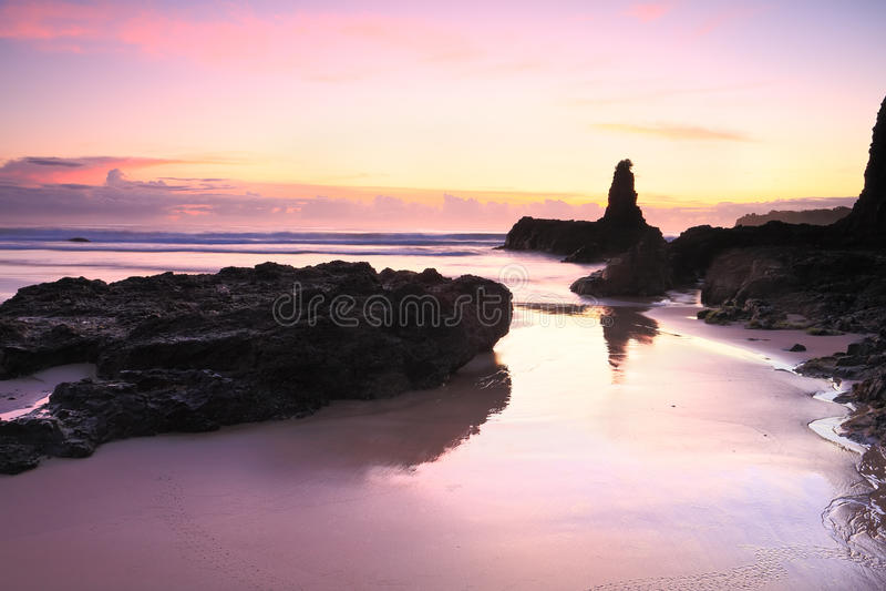 Sunrise reflections in tidal wet sands Jones Beach Kiama. Beautiful sunrise skies and reflected colours in the tidal wet sands. Jones Beach, Kiama Downs stock photography