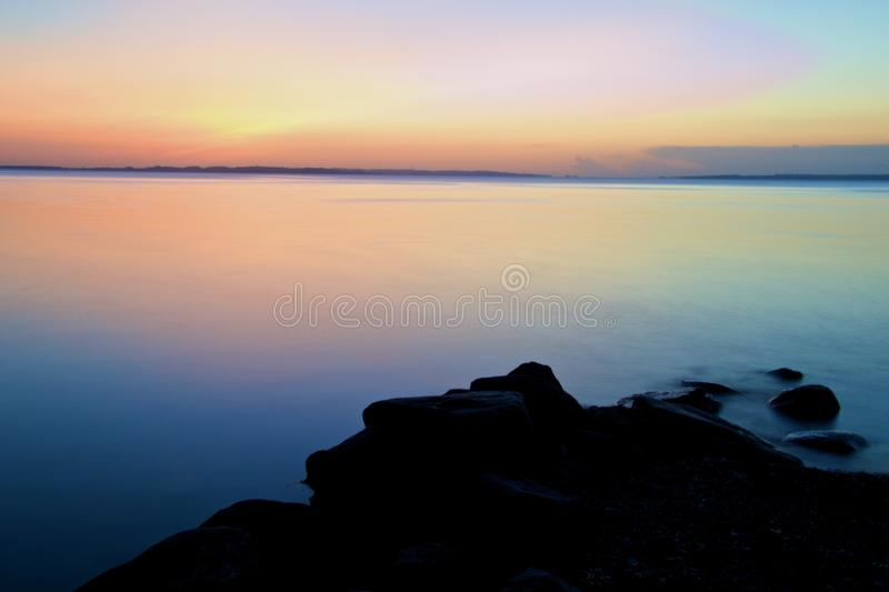 Sunrise with rocks. A view from Moesgaard beach, Denmark. Early morning long exposure stock photos