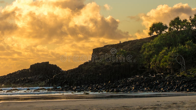 Sunrise rocky coastline. Boy on rocky coastline at sunrise Fingal Head Australia royalty free stock images