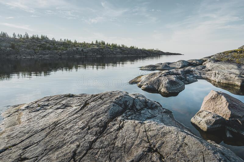 Sunrise on a rocky shore. Still water. Pine forest in the background royalty free stock photos