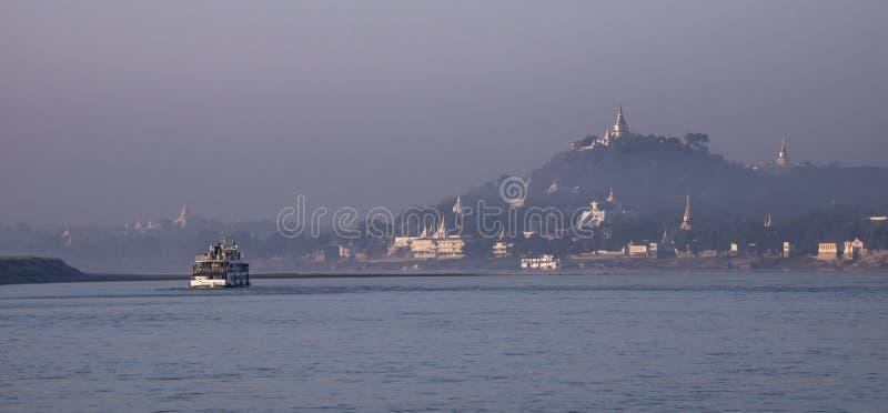 Sunrise at Sagaing on the Irrawaddy. Boat passing at the Irrawaddy during sunrise along the stupas of Sagaing, Myanmar royalty free stock image