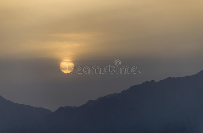 Sunrise during a sand storm above mountains stock photography