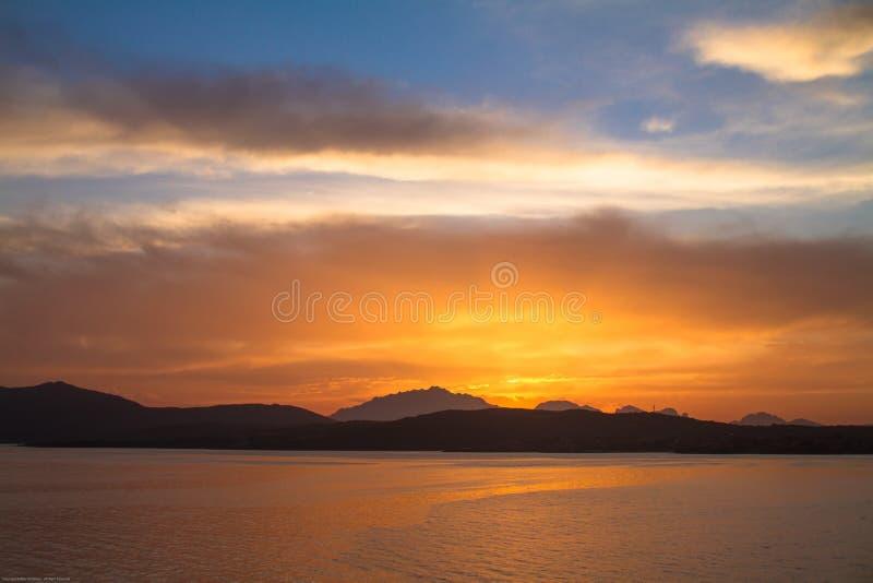 Sunrise on the Sardinian sea coast with intense orange color seen from the sea. Sunrise on the Sardinian sea coast with intense orange color seen from sea stock image