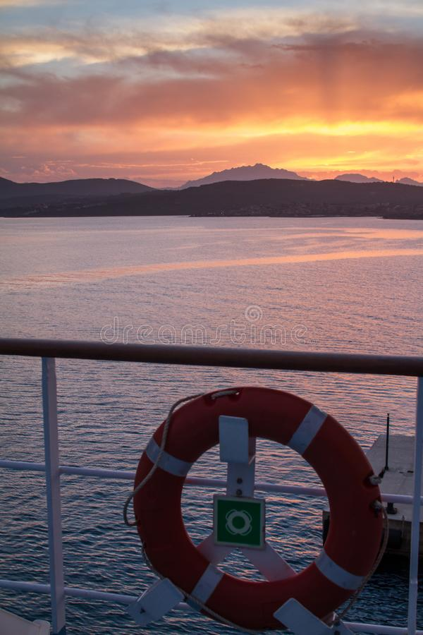 Sunrise on the Sardinian sea coast with intense orange color seen from the sea on the ferry that is about to dock with lifebuoy in. Sunrise on the Sardinian sea royalty free stock photos