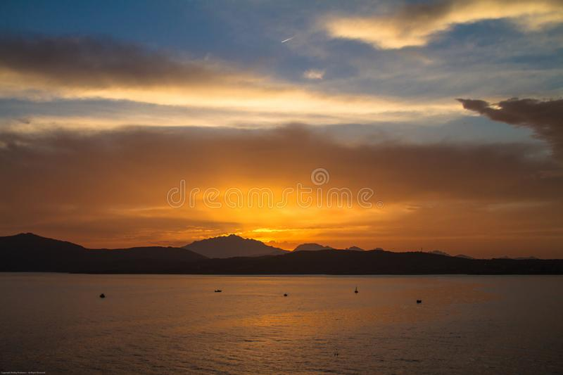 Sunrise on the Sardinian sea coast with intense orange color seen from the sea with five fishing boats on flat water. Sunrise on the Sardinian sea coast with stock photography