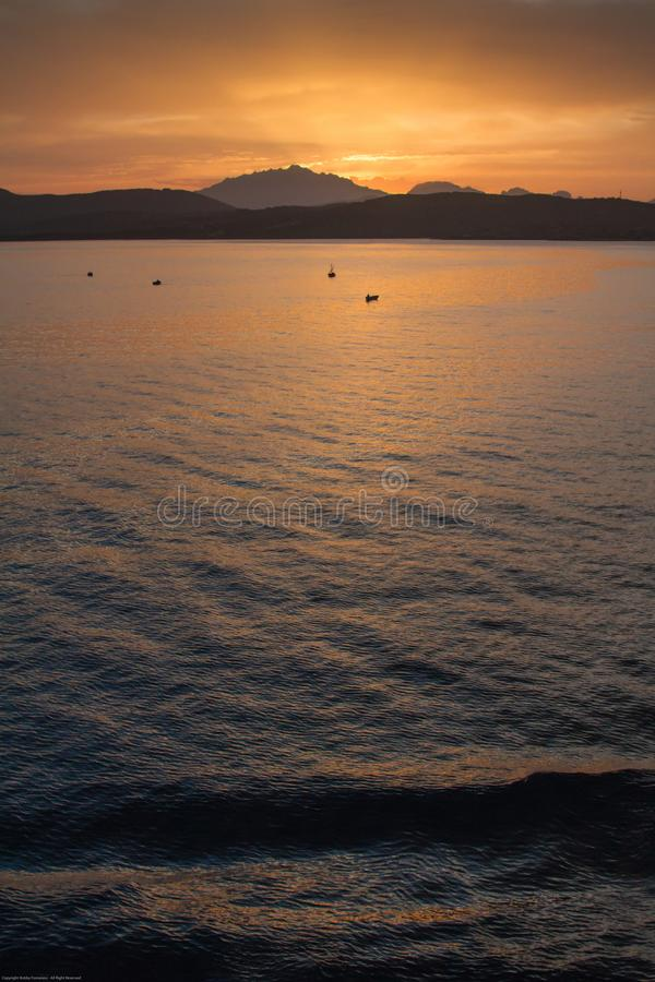 Sunrise on the Sardinian sea coast with intense orange color seen from the sea with five fishing boats on flat water. Sunrise on the Sardinian sea coast with royalty free stock photos