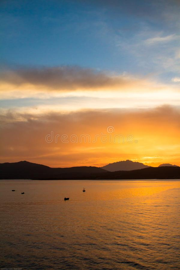 Sunrise on the Sardinian sea coast with intense orange color seen from the sea with five fishing boats on flat water. Sunrise on the Sardinian sea coast with royalty free stock image