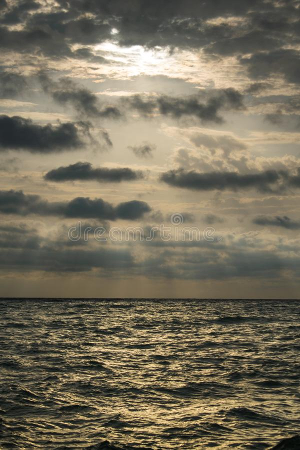 Sunrise at sea, with a dramatic sky full of black clouds. A stormy summer day stock photo