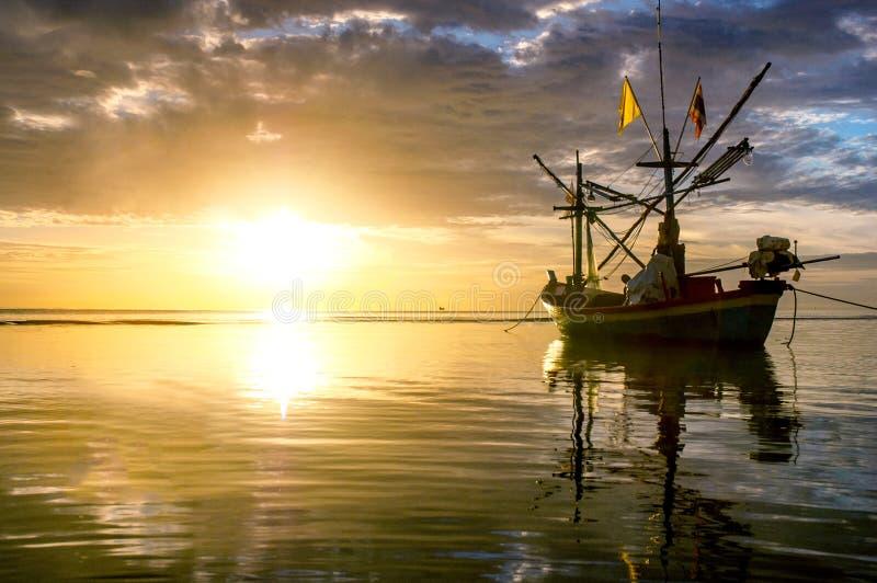 Sunrise at sea with native fisherman boat stock photo