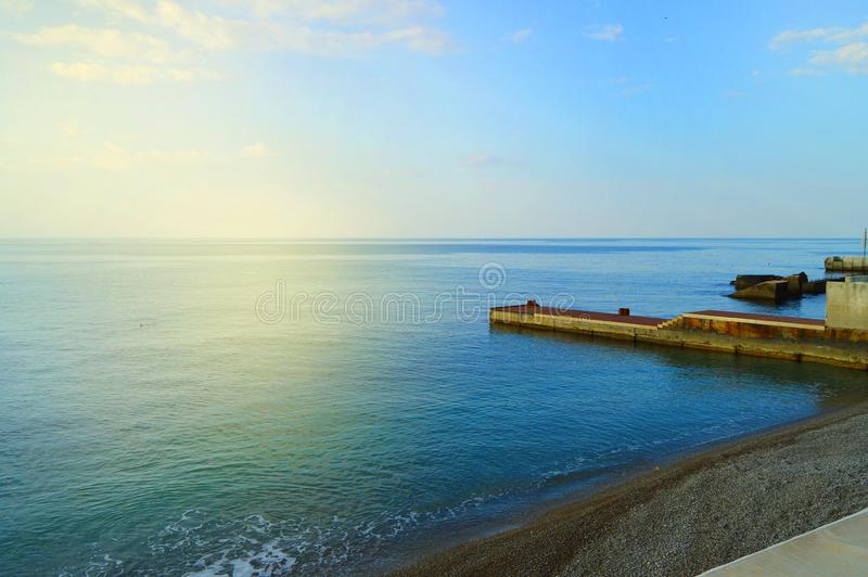 Sunrise on the sea with sun glare, pier on the shore in the early morning, calm, rest, summer holiday concept royalty free stock photography