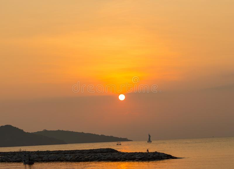 Sunrise at sea. variety of colors. And hues of the rising sun, Reflections on the sea,There are boats and bicycles on a small rocky island. Behind have stock images