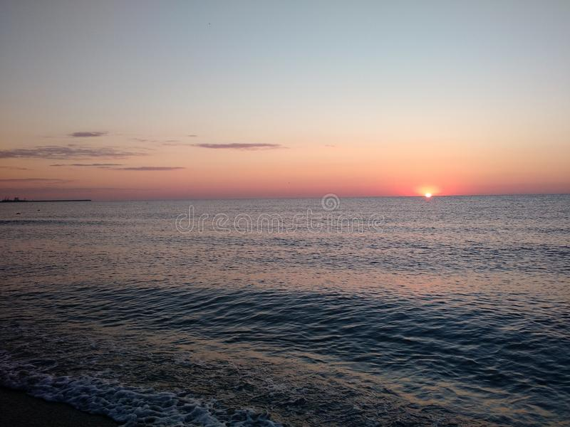 Sunrise seen from a beach rushed by sea waves stock photo