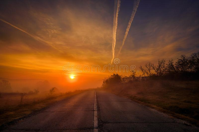 Sunrise seen from a country road with cracks during autumn with dramatic fog and clouds stock photo
