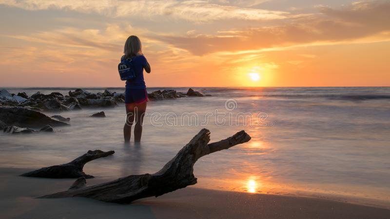 Sunrise seen from the sand, with the silhouette of a woman photographing sunrise, stones leaving the sea and a log buried in the stock images