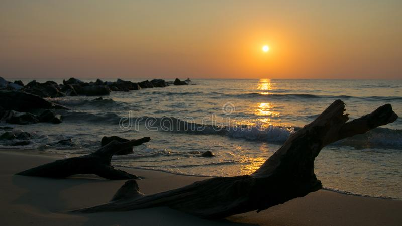 Sunrise seen from the sand, stones leaving the sea and a log buried in sand on the shore of the Mediterranean Sea royalty free stock photography