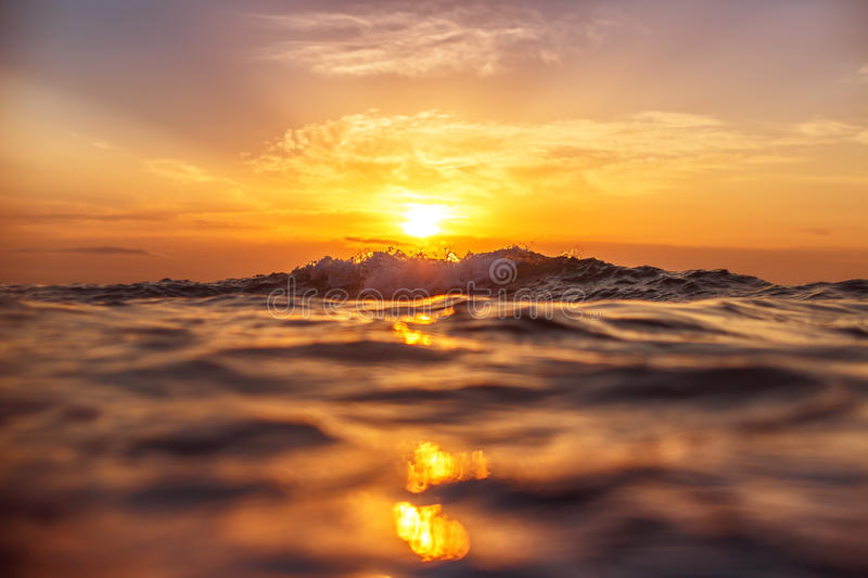Sunrise and shining waves in ocean royalty free stock photography