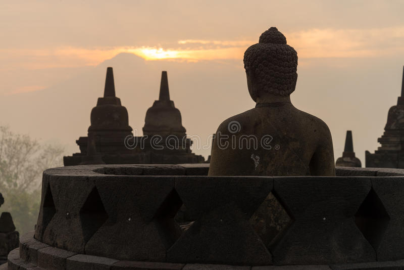 Sunrise silhouette buddha sculpture in open stupa royalty free stock photo