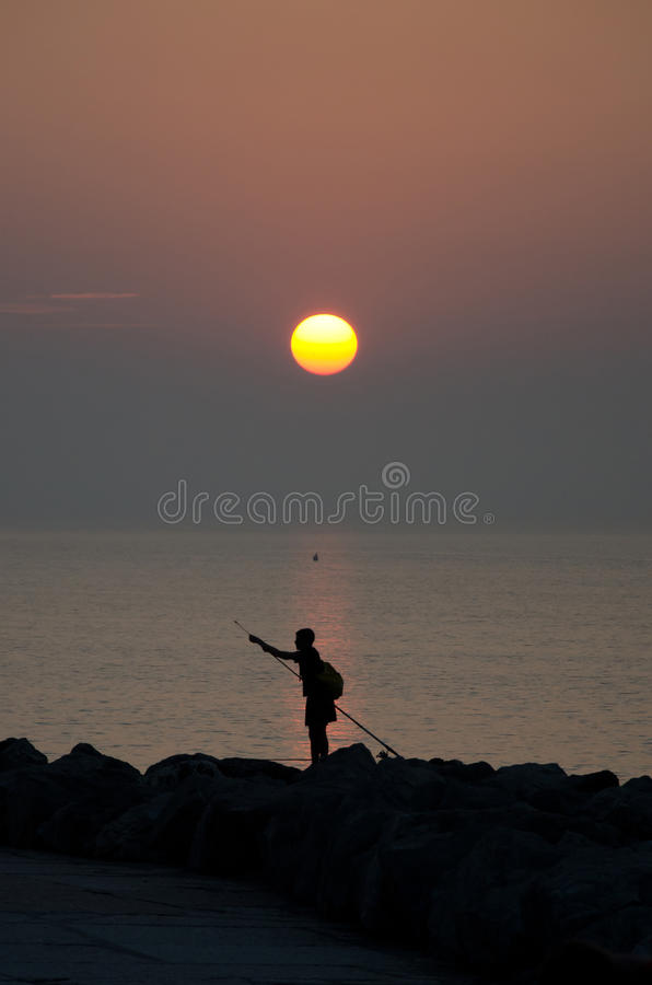 Sunrise with a silhouette of a fisherman, Caorle, Italy, stock photos