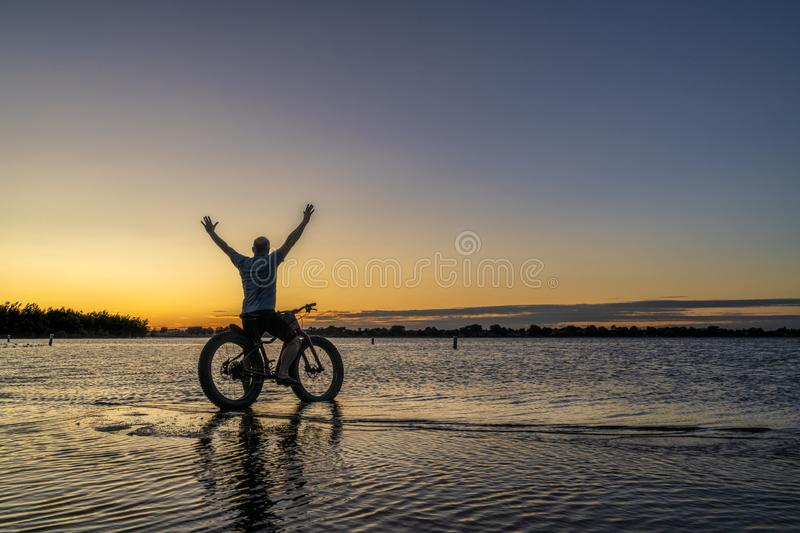 Sunrise silhouette of a man with fatbike. Sunrise silhouette of a man with a fat mountain bike on a lake shore, Boyd Lake State Park in northern Colorado stock photos