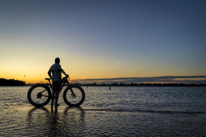 Sunrise silhouette of a man with fatbike. Sunrise silhouette of a man with a fat mountain bike on a lake shore, Boyd Lake State Park in northern Colorado stock image