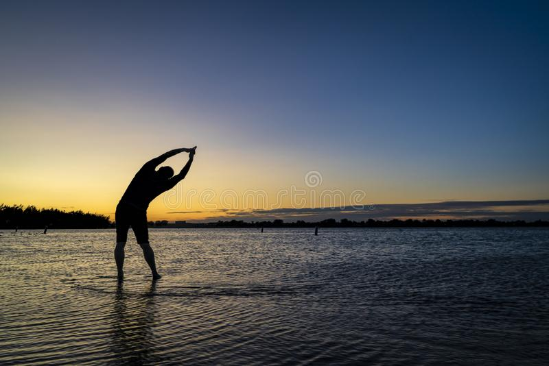 Sunrise silhouette of a man on a lake. Practicing yoga palm tree pose - sunrise silhouette of a man on a lake beach, Boyd Lake State Park in northern Colorado stock photo